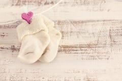 与桃红色心脏的被编织的婴孩袜子木表面上 免版税库存照片