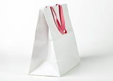 与桃红色把柄的白色购物袋 免版税库存图片