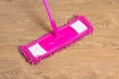 与桃红色拖把的清洗的木地板 免版税库存照片