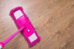 与桃红色拖把的清洗的木镶花地板 免版税图库摄影