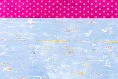 与桃红色星形状样式织品边界的老浅兰的木背景 库存图片