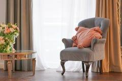 与桃红色枕头和花的灰色椅子在屋子里 免版税库存照片