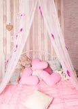 与桃红色枕头的有四根帐杆的卧床床 库存图片