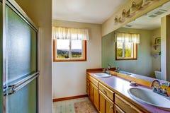 与桃红色桌面和两个水槽的典雅的卫生间内部 库存照片