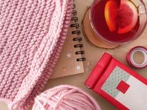 与桃红色毛线、围巾和笔记薄的热的茶 免版税库存图片