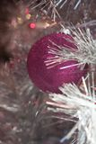 与桃红色洋红色装饰品和光的寒假银白色闪亮金属片圣诞树 库存图片