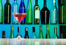 与桃红色液体的玻璃在酒吧桌上站立  免版税库存图片