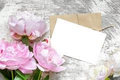与桃红色牡丹的空白的白色贺卡开花花束和信封在白色木背景 平的位置 顶视图 库存照片