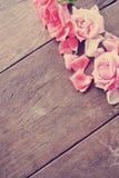 与桃红色玫瑰和玫瑰花瓣的土气木桌 免版税库存照片