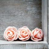 与桃红色玫瑰框架的木背景 免版税库存图片