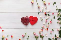 与桃红色玫瑰的华伦泰背景开花和在白色土气木头的手工制造心脏夫妇 免版税库存图片