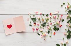 与桃红色玫瑰的华伦泰背景开花心脏,在白色土气木头的手工纸卡片 库存图片