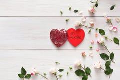 与桃红色玫瑰的华伦泰背景开花,在白色土气木头的手工制造心脏夫妇 库存图片
