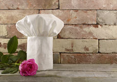 与桃红色玫瑰的无边女帽在砖墙上 免版税库存照片