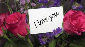 与桃红色玫瑰的被分类的花与贺卡'我爱你'说明 股票录像