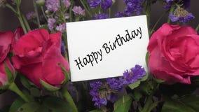 与桃红色玫瑰的被分类的花与贺卡'生日快乐'说明 股票录像