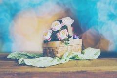 与桃红色玫瑰的静物画在篮子 免版税库存图片