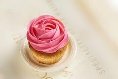 与桃红色玫瑰色装饰的杯形蛋糕 图库摄影