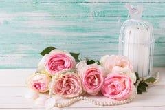 与桃红色玫瑰花、珍珠和蜡烛的背景在得体 库存图片