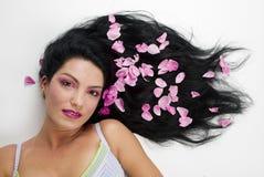 与桃红色玫瑰花瓣的黑发 免版税库存照片