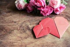 与桃红色玫瑰花的心脏形状在木桌上 免版税库存图片