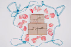 与桃红色瓣的两个礼物inparchment和最高荣誉在白色背景 顶视图,平的位置 库存图片