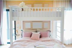 与桃红色的一张白色木床把枕在和在墙壁上的框架我 免版税库存照片