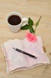 与桃红色的一本日志上升了,笔和杯子 免版税库存图片