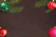与桃红色的圣诞树分支,在黑暗的背景的红色波浪和绿色有肋骨球 免版税库存图片