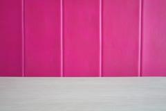 与桃红色皮革沙发的白色木纹理桌 库存照片