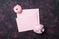 与桃红色纸空白和美丽的毛茛属花的创造性的构成在婚姻的大模型舱内甲板位置的黑台式视图 库存照片
