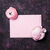 与桃红色纸空白和美丽的毛茛属花的创造性的构成在黑桌上顶上为婚姻的大模型舱内甲板位置 免版税库存图片