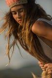 头戴与桃红色羽毛的女孩当地印地安头饰 免版税库存图片