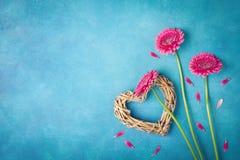 与桃红色花、心脏和瓣的春天背景 贺卡为妇女天 平的位置样式 顶视图 库存照片