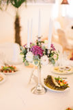 与桃红色花、玻璃和蜡烛的欢乐婚礼桌设置 免版税库存照片