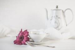 与桃红色花和软的织品的正式茶具 免版税库存照片