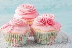 与桃红色花的杯形蛋糕 库存照片
