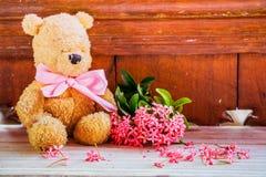 与桃红色花的玩具熊与软的作用 免版税库存照片