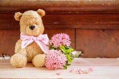 与桃红色花的玩具熊与软的作用 库存图片