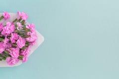与桃红色花的白色信封在蓝色背景 邮寄您 免版税图库摄影