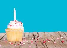 与桃红色蜡烛和重点的杯形蛋糕洒 免版税库存图片