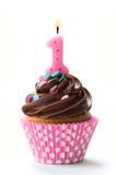 与桃红色蜡烛的第一块生日杯形蛋糕 库存照片