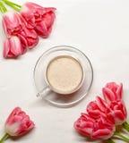与桃红色郁金香和一个杯子的Flatlay在白色背景的可可粉 免版税库存图片