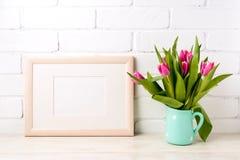 与桃红色郁金香的木风景框架大模型在水罐 库存照片