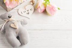 与桃红色郁金香的玩具熊 免版税库存照片