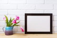 与桃红色郁金香的黑棕色风景框架大模型在紫色bl 库存图片