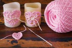 与桃红色钩针编织手工制造心脏的两个蜡烛圣徒华伦泰的 免版税库存图片