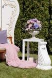 与桃红色,蓝色,紫罗兰色玫瑰的花卉婚礼装饰在花瓶 库存照片