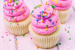 与桃红色结霜的生日杯形蛋糕 免版税图库摄影