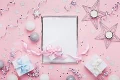 与框架、假日球、礼物盒和衣服饰物之小金属片的圣诞节大模型在时髦的桃红色台式视图 时尚欢乐背景 免版税图库摄影